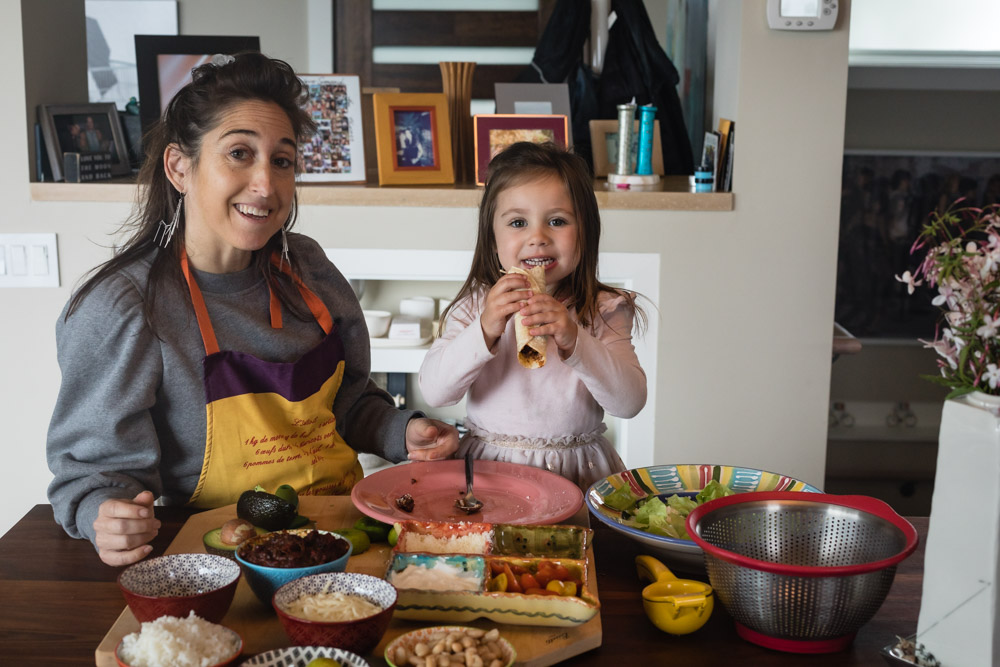 Mom and daughter make tacos together at the kitchen table. Photo contribute by Daniela Gerson of Waves in the Kitchen.
