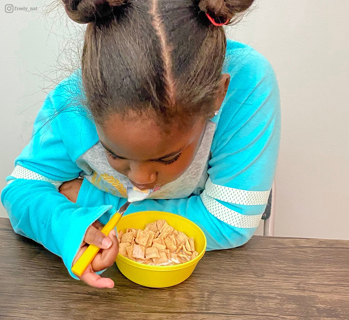 Young girl enjoys a bowl of milk and cereal. Photo contribute by @freely_nat.