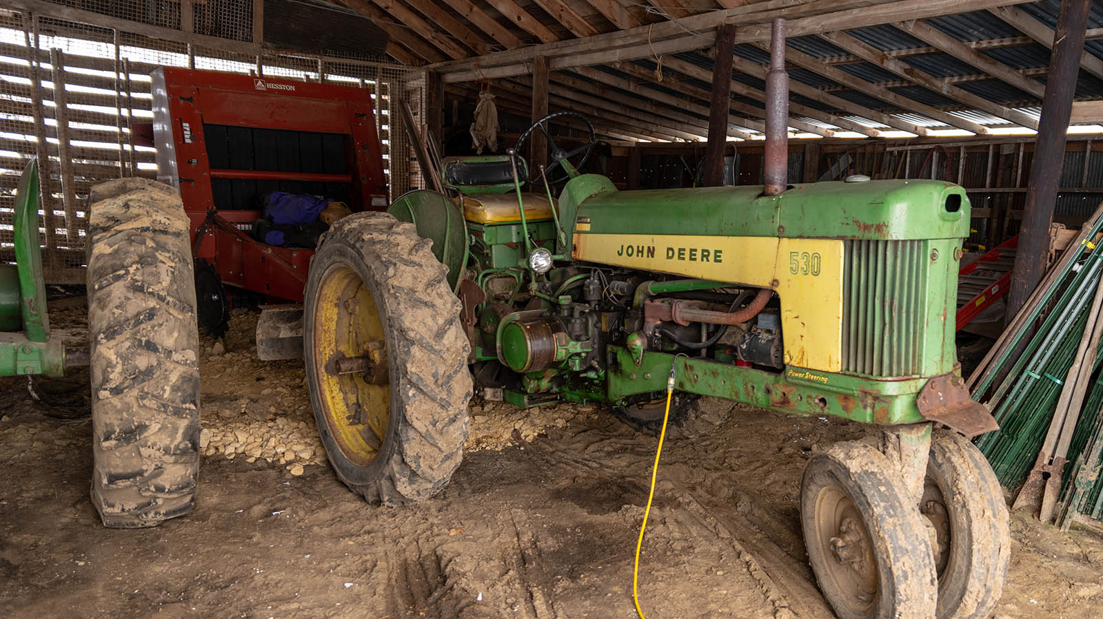Old green John Deere diesel tractor in the barn with an electrical cord coming out of the engine.