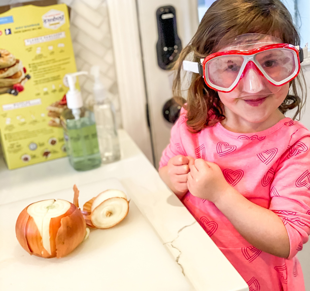 Young girl in goggles cuts up an onion in the kitchen.