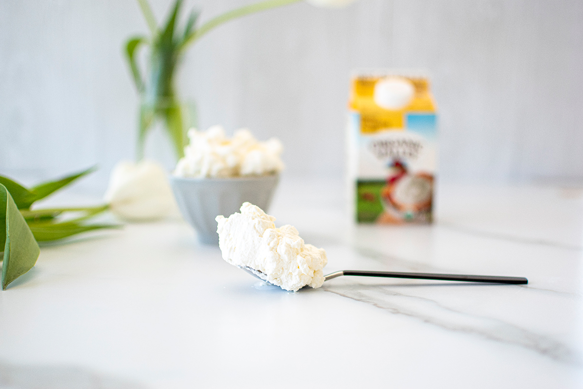 Stiff peaks of whipped cream shown on a spoon after whipping.