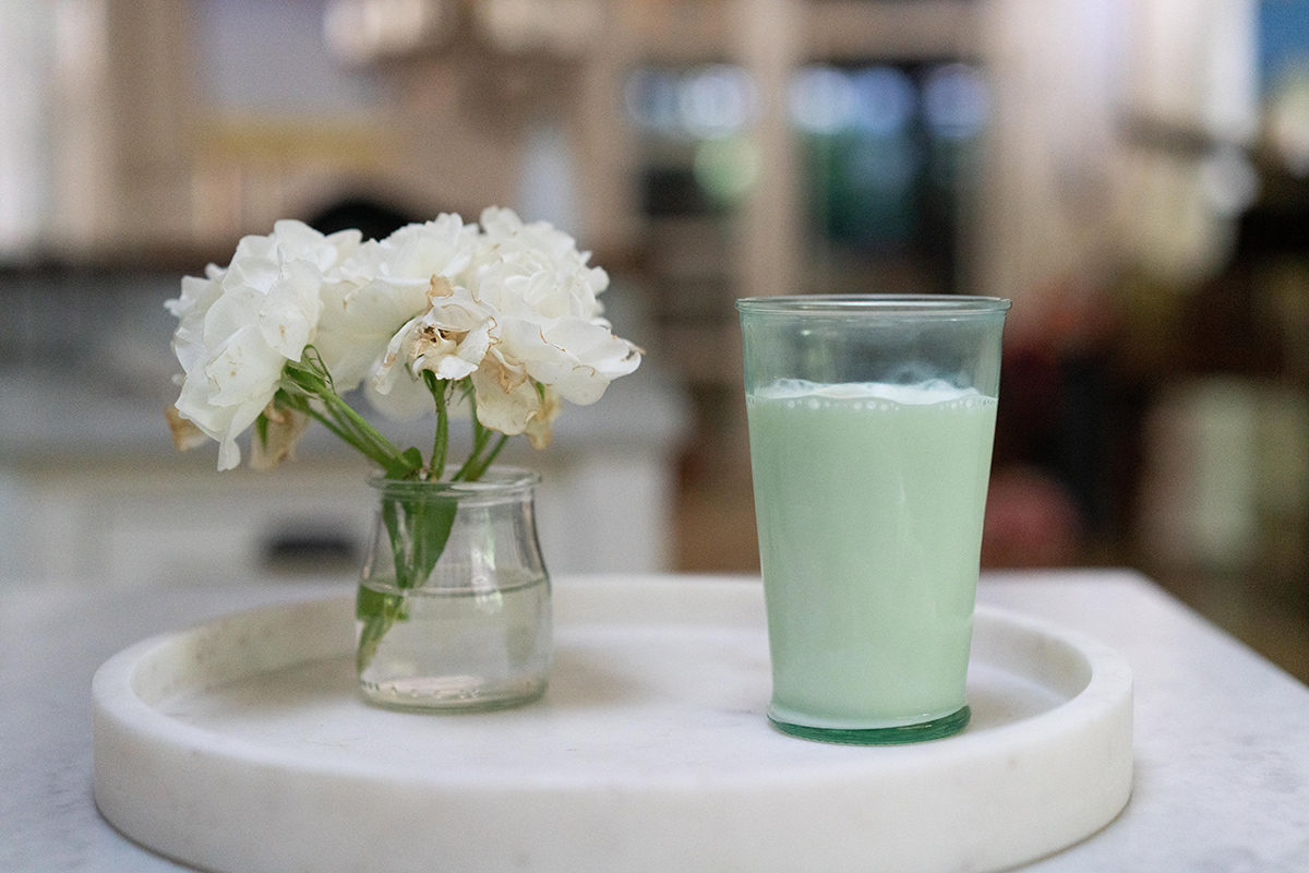 Glass of Organic Valley milk next to a boquet of white flowers.