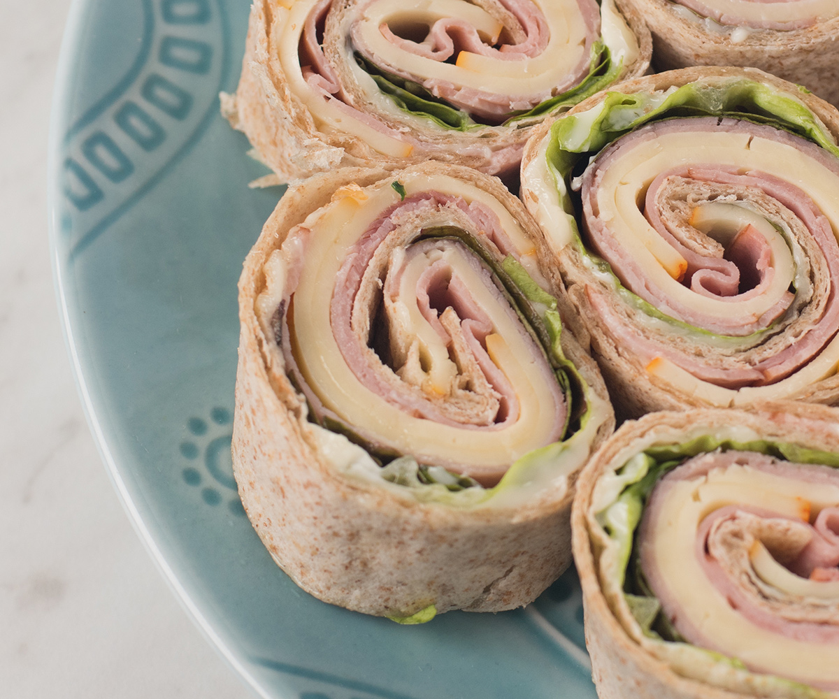 A wrap containing organic lunchmeat slices, sliced cheese and lettuce cut in slices and laid on a plate so they look like pinwheels.