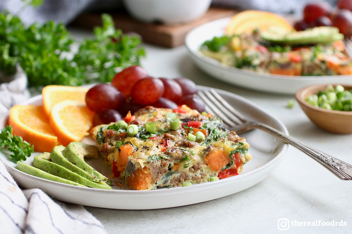A square of sausage and vegetable egg bake on a white plate with sliced avocado, sliced oranges, and grapes.