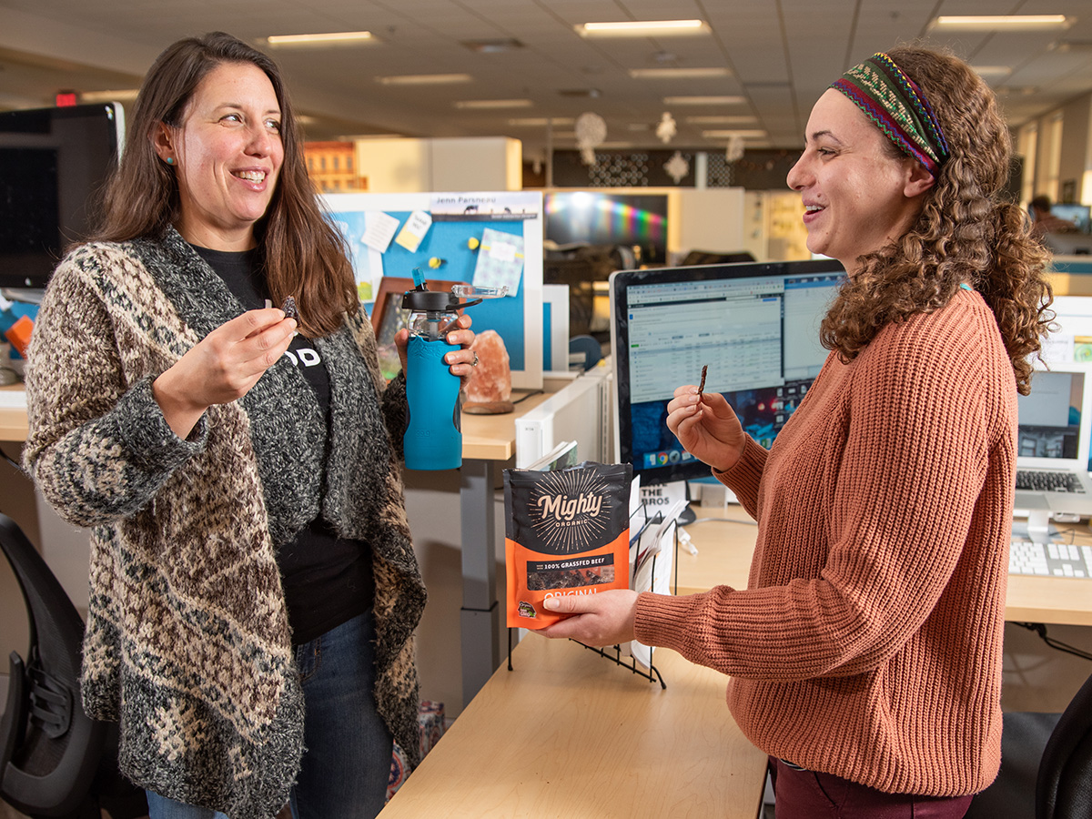 Two woman snack on Mighty Organic beef jerky while laughing in the office.