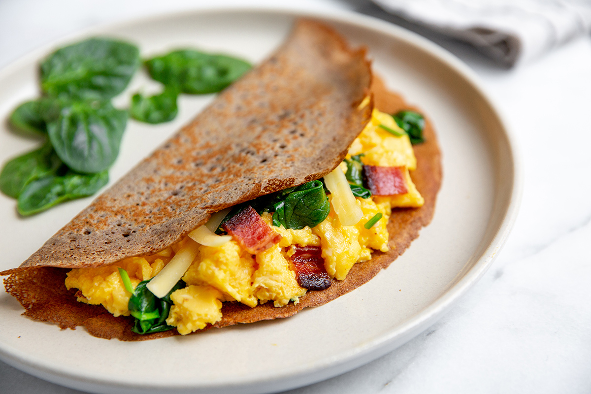 Savory gluten-free crepes filled with scrambled eggs, cheese, spinach and bacon.