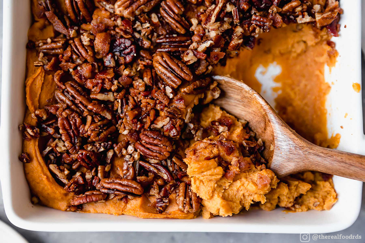 A wooden spoon scoops out orange sweet potato casserole topped with whole pecans.