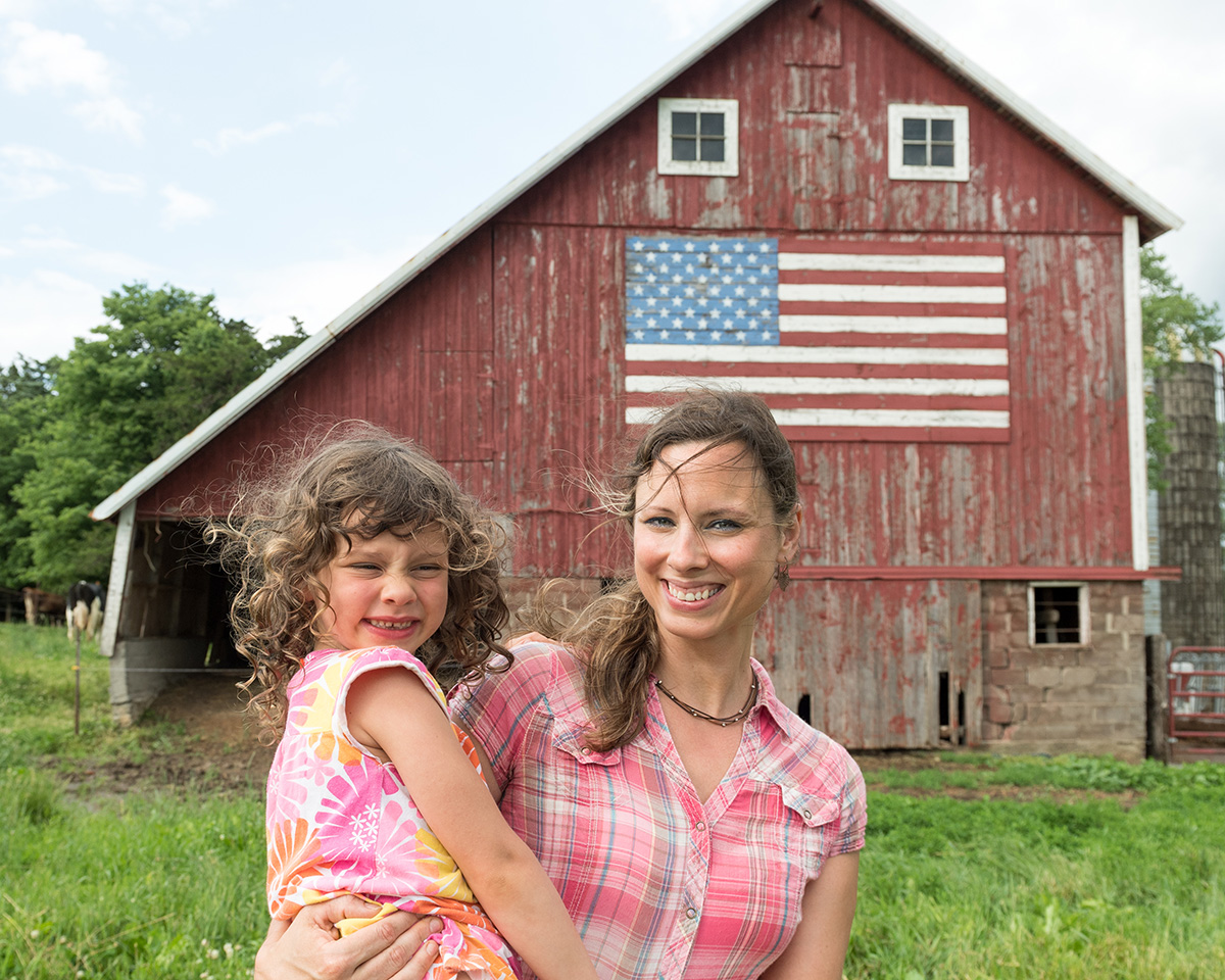 Mom Heidi Vosberg holds daughter Rachel in front of their red barn with an American flag painted on it.