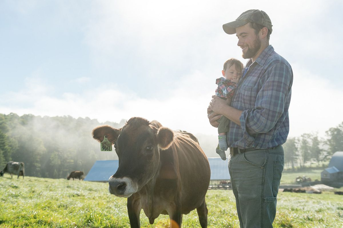 Henry Pearl holds his youngest son while next to a cow in their organic pasture on the Vermont farm.