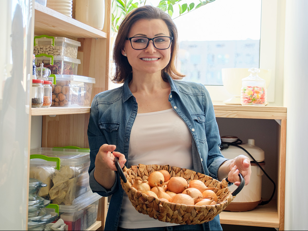 Women holds a basket of organic in her pantry.
