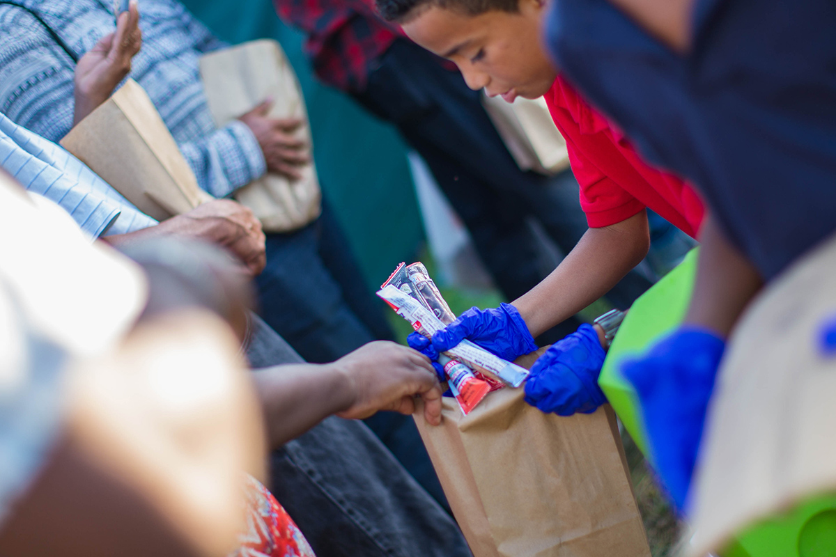 Young child hands food to those in need.