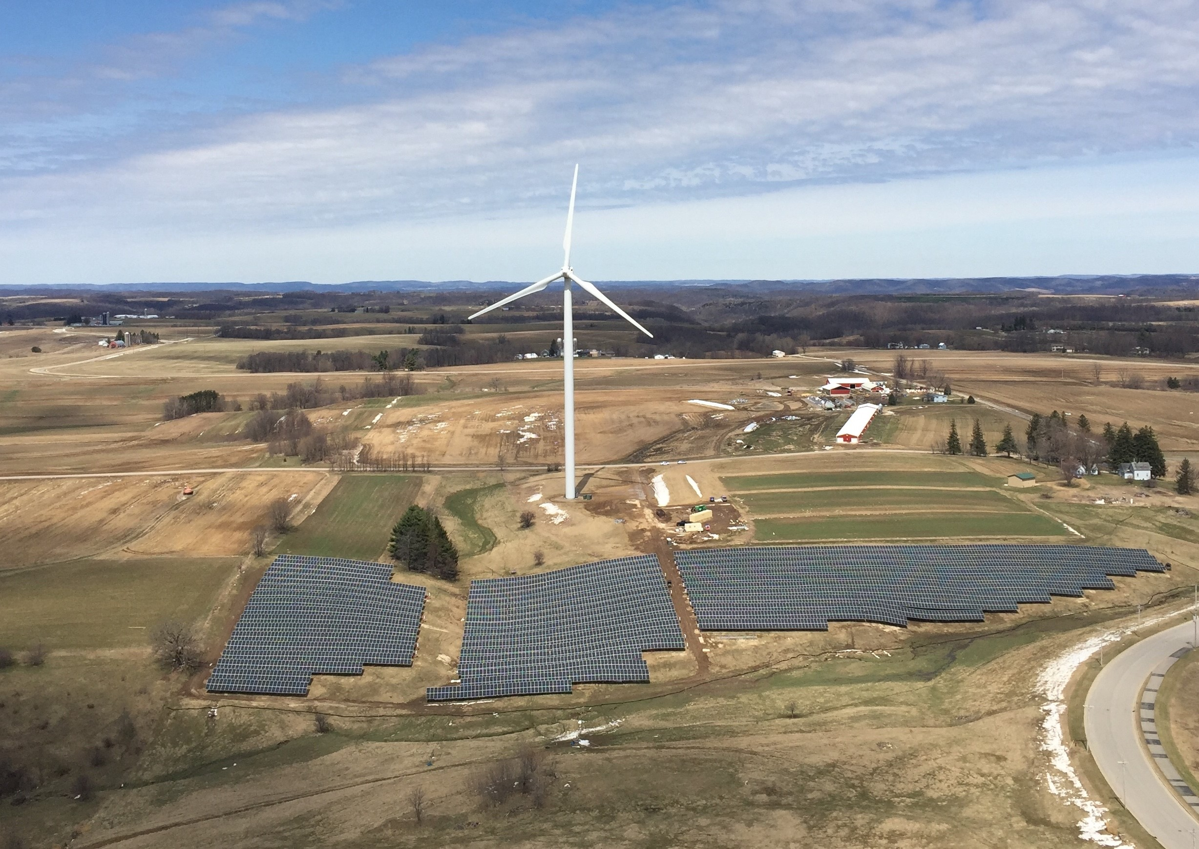 An aerial view of solar panels arrayed underneath a white wind turbine with brown ground and a little snow.