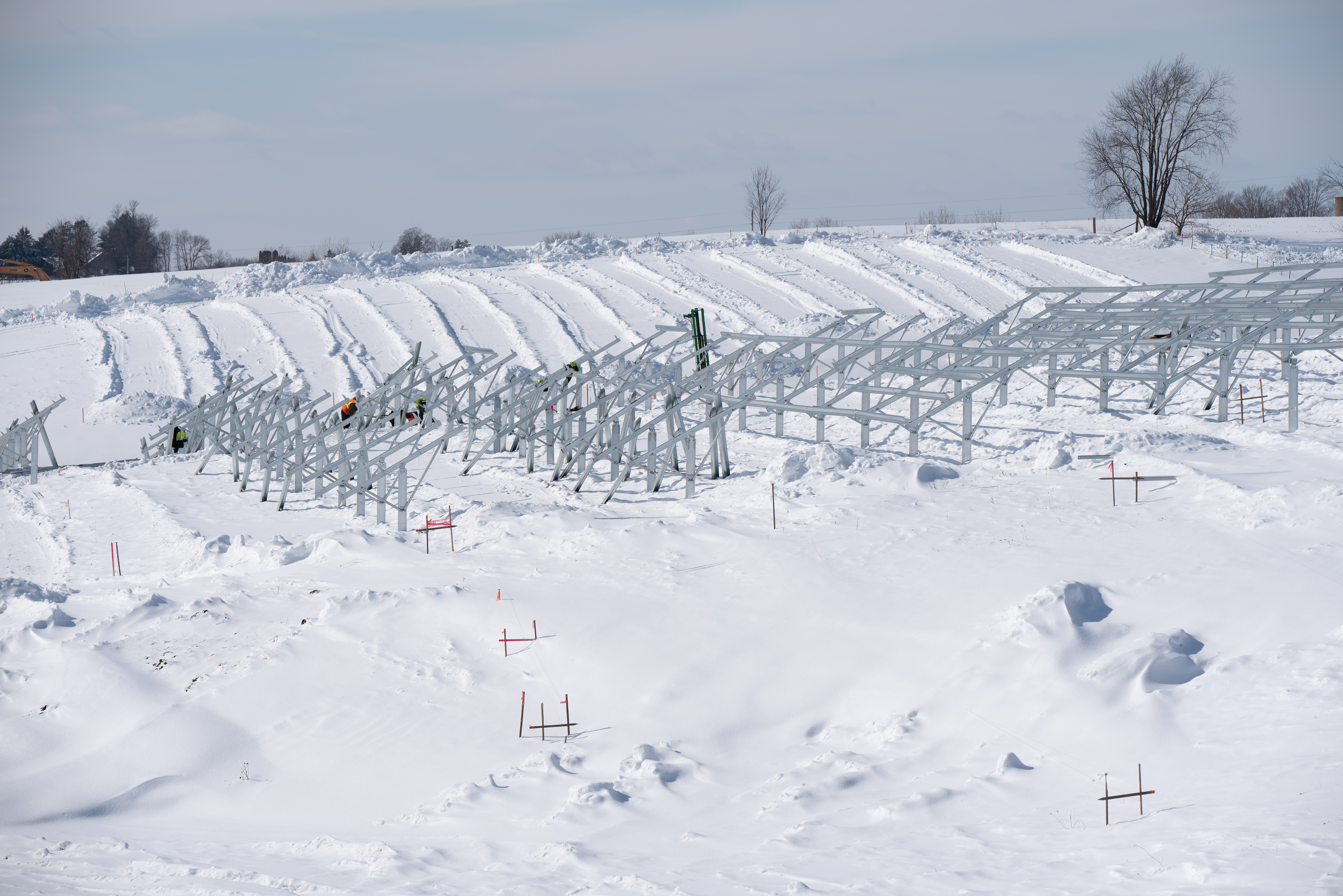 Workers installing the supports for solar panels in a snow-covered field.
