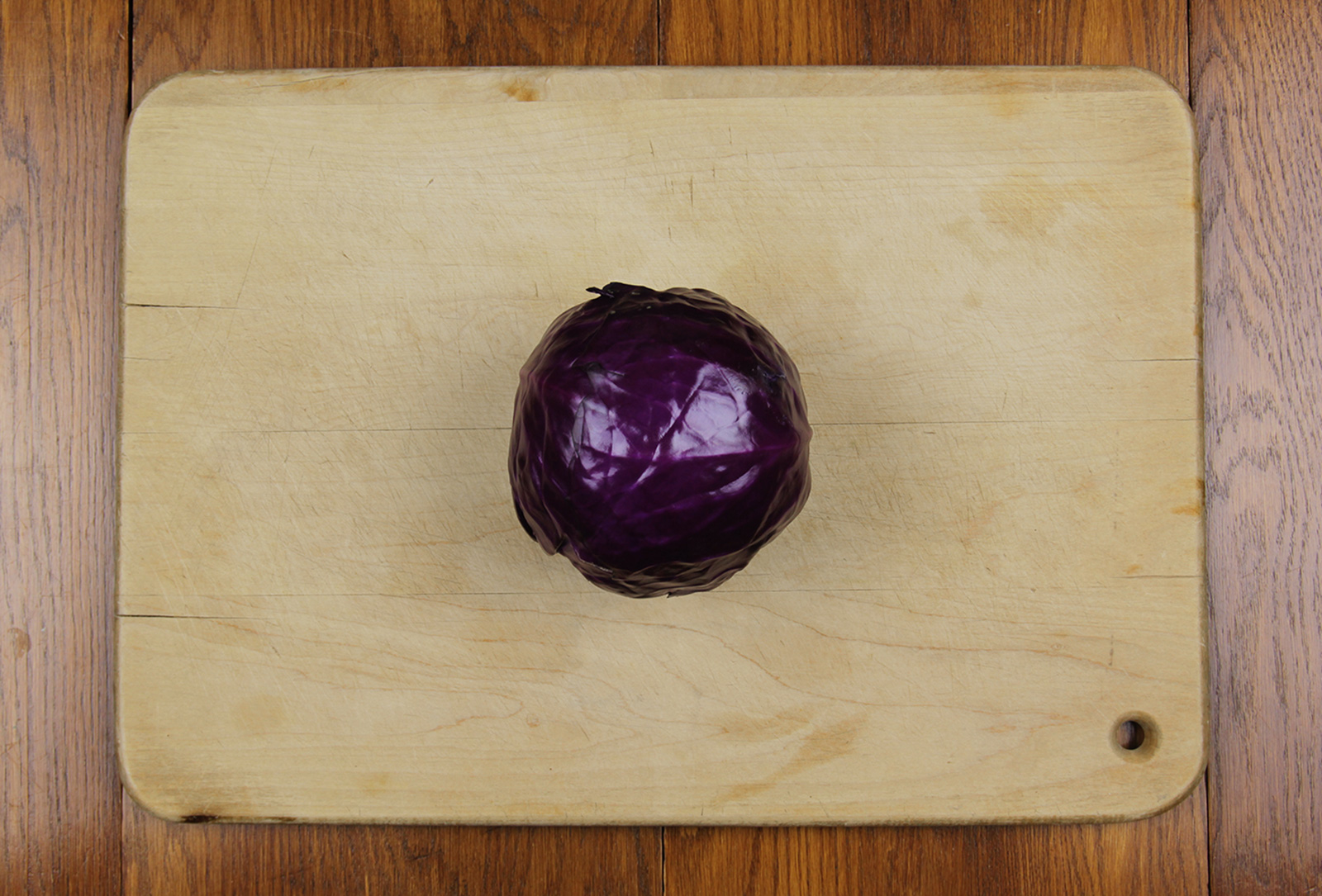 Purple head of cabbage on a cutting board.