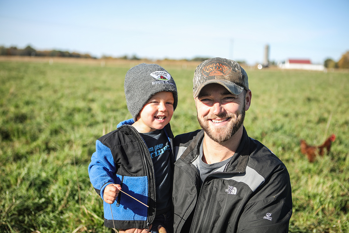 Organic Valley farmer, Jordan Settlage smiles holding his son in the pasture of his farm.