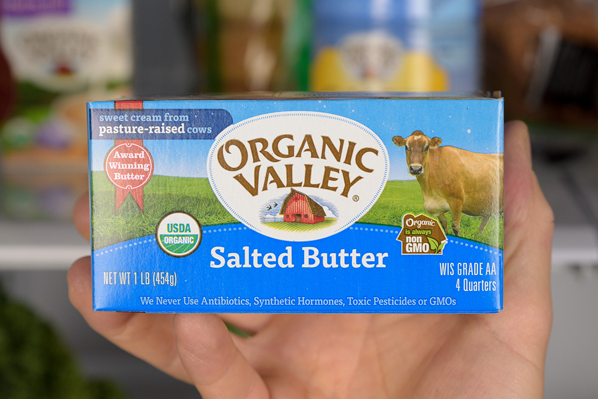 Organic Valley organic butter in front of a stocked fridge.