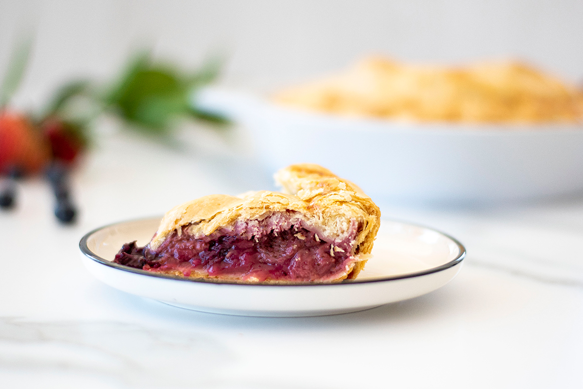 Slice of triple berry pie served and ready to eat.