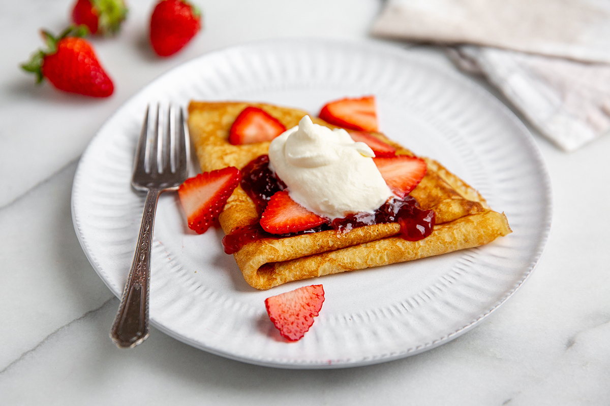Sweet crepes topped with fresh homemade whipped cream, strawberries and jam.