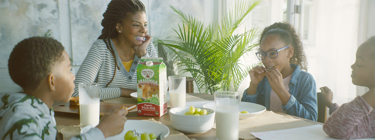 Family sits around the table enjoying grilled cheese and Organic Valley Grassmilk.