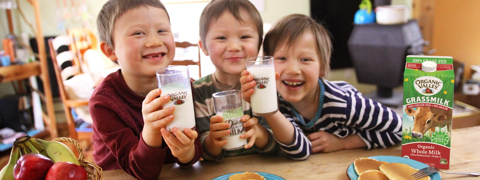 Asian children smile with glass of milk in hand.