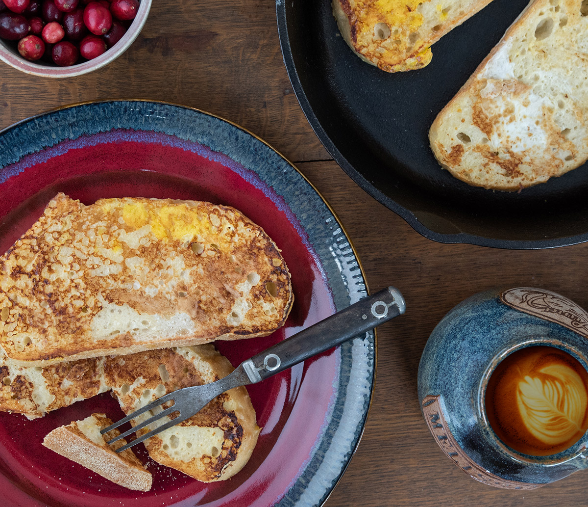 Eggnog french toast on colorful stoneware plates with a cup of coffee nearby.