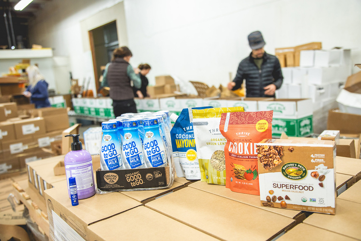 Donated food products sit on a table in a warehouse.