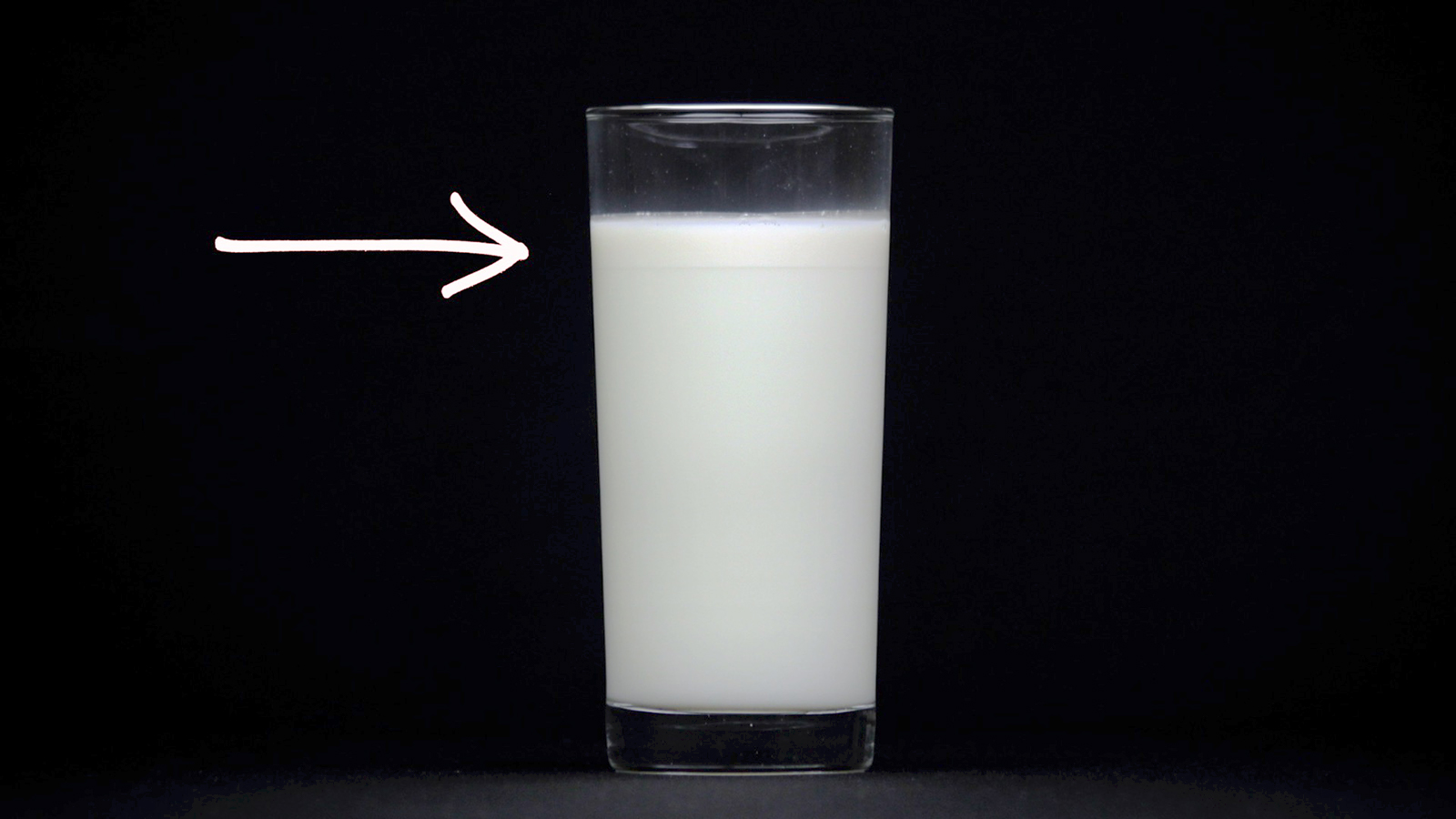 Glass of milk with cream on top.