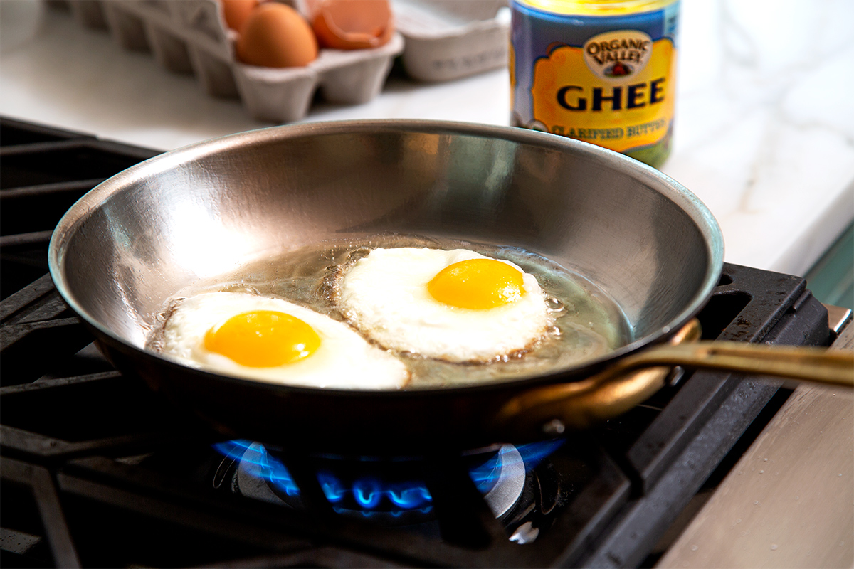 Two fried eggs sizzle in a pan with Organic Valley ghee.