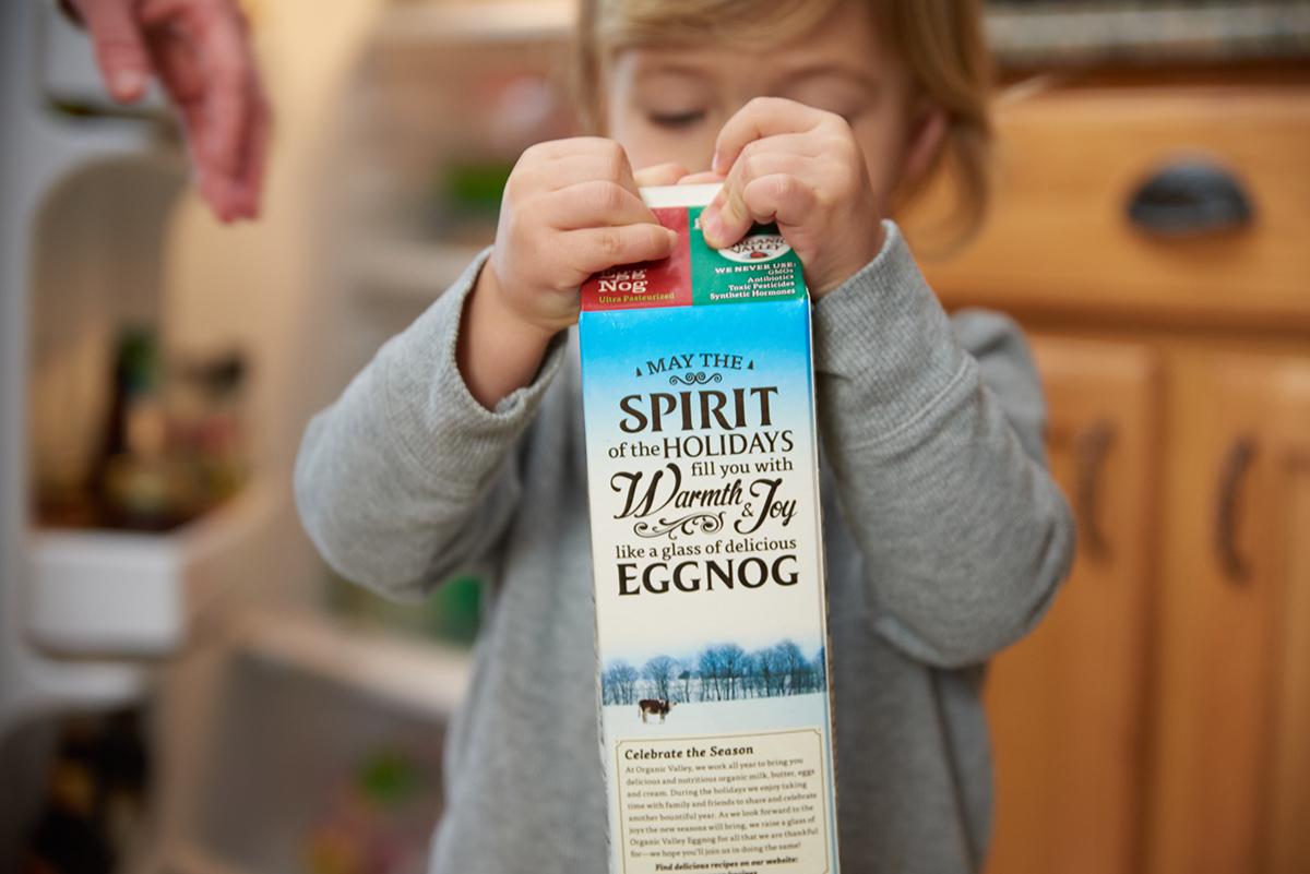 A little boy holds an eggnog carton that says may the spirit of the holidays fill you with warmth and joy like a glass of delicious eggnog.