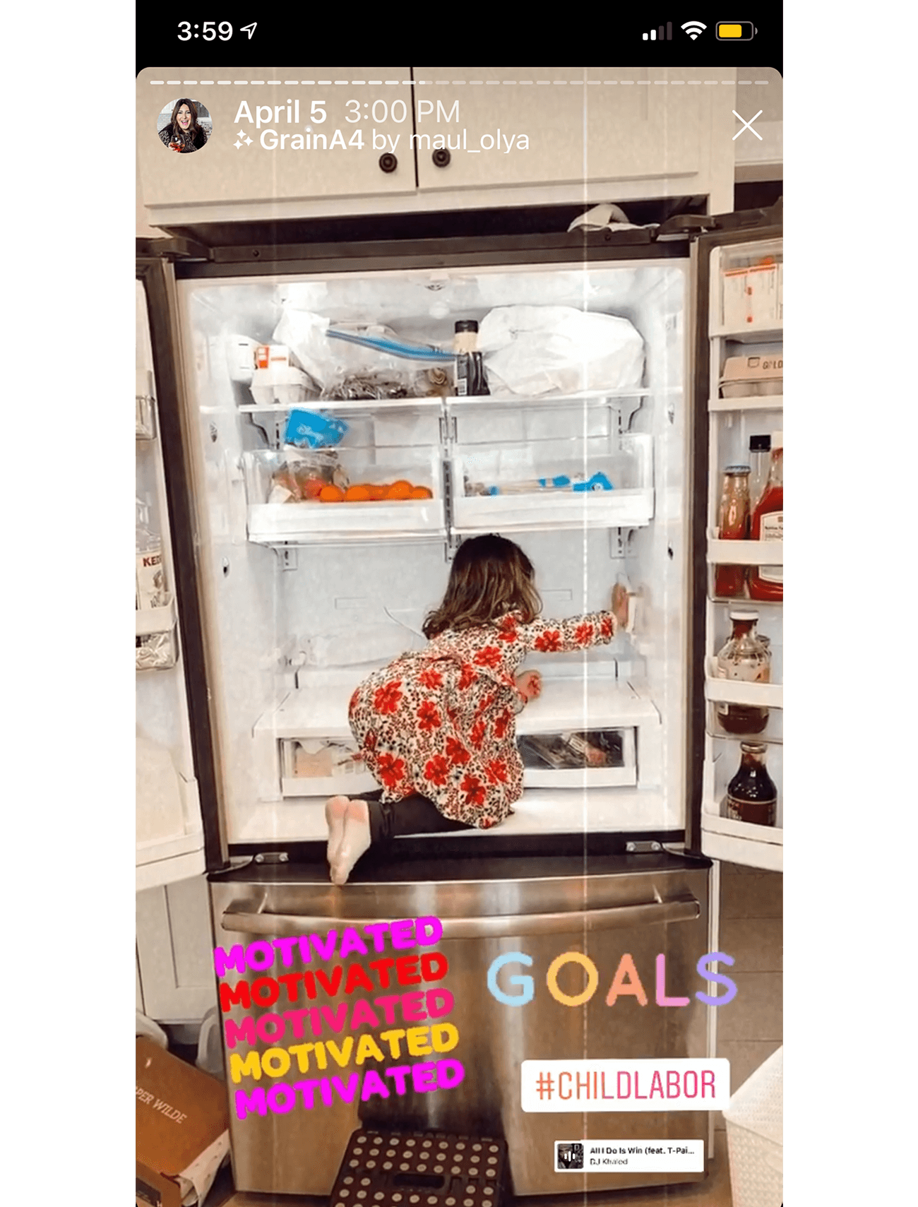 A little girl is kneeling inside the fridge while cleaning the shelves.