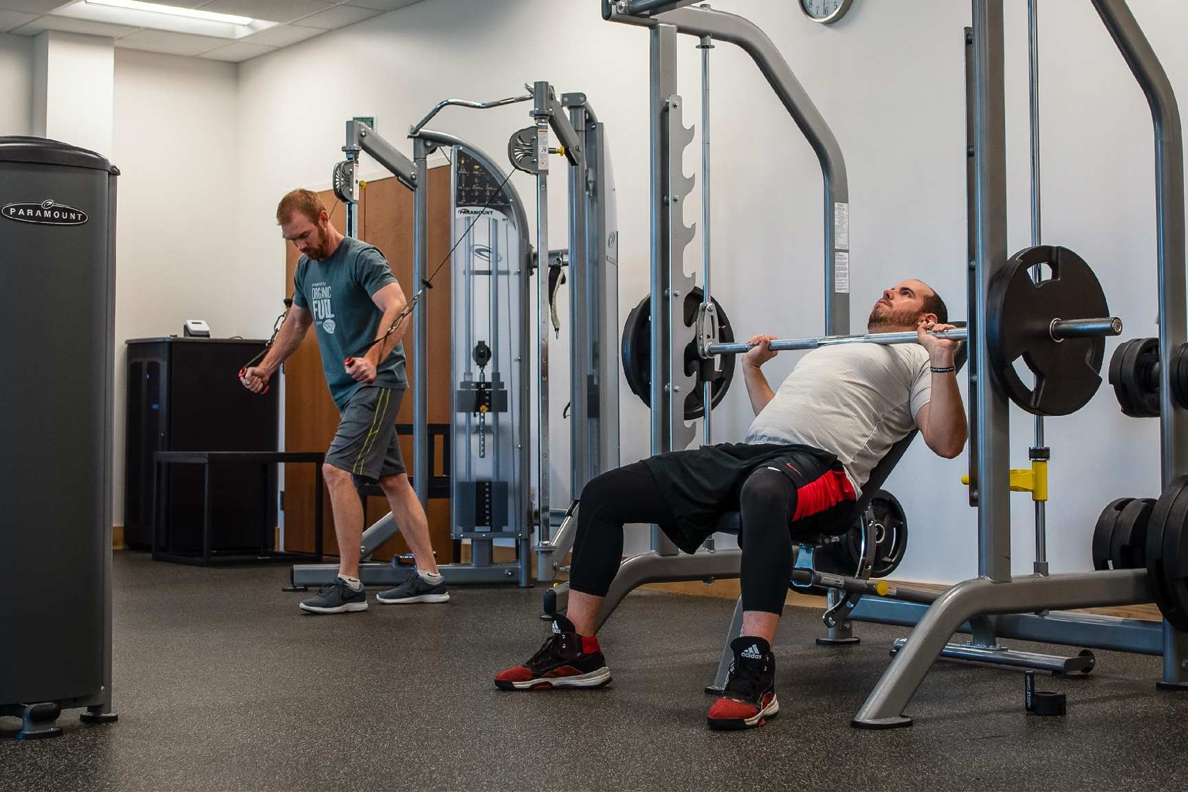 Two men work out on gym equipment.