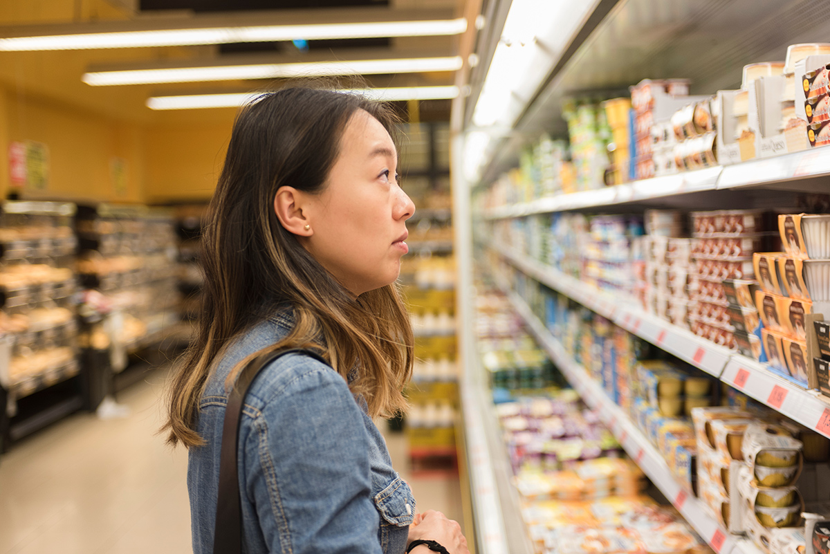 A woman stands in front of the dairy case in a grocery store and looks at the options.