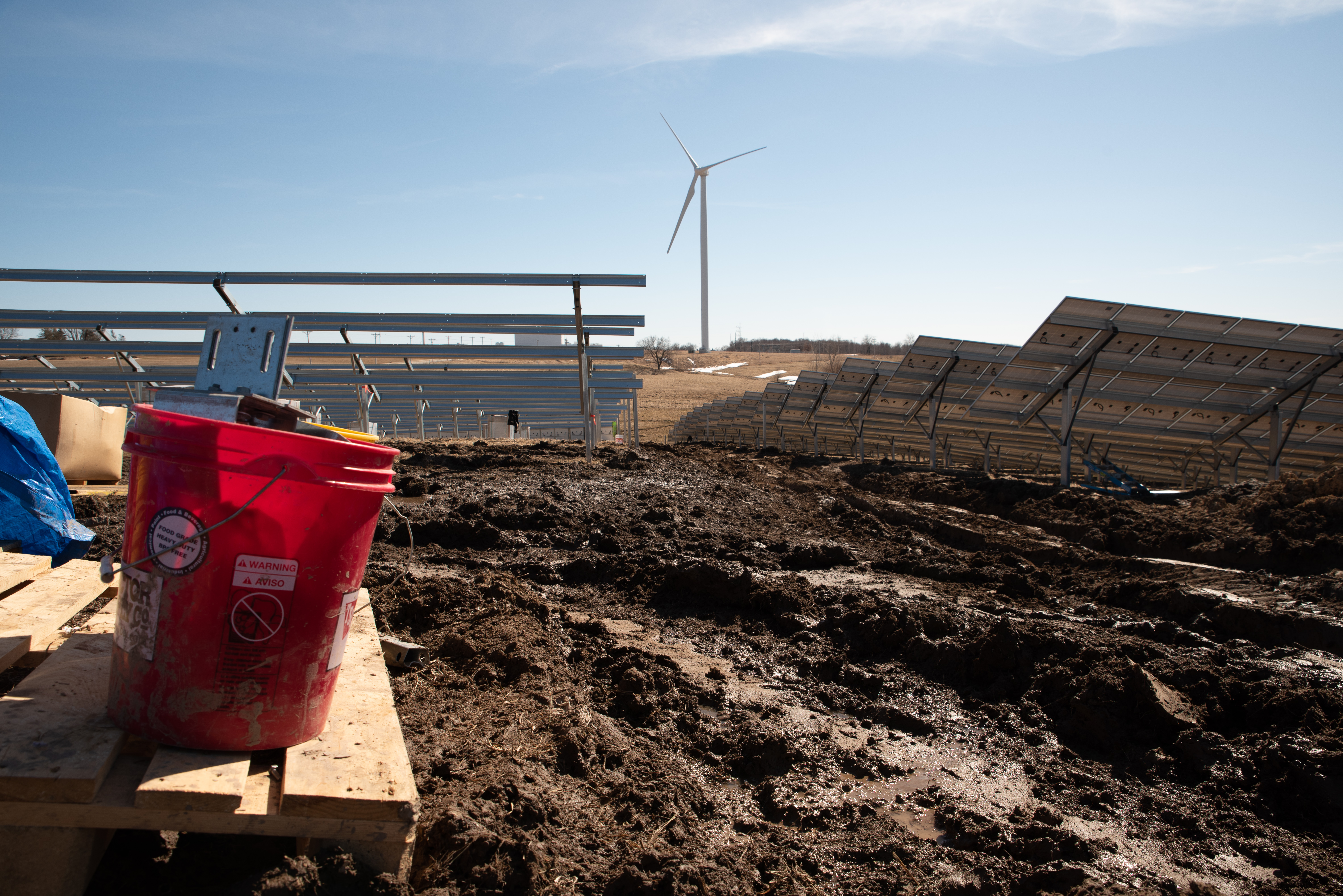 A red bucket on a table overlooking a field of churned, muddy ground, with partially assembled solar panels in rows and a wind turbine in the distance.