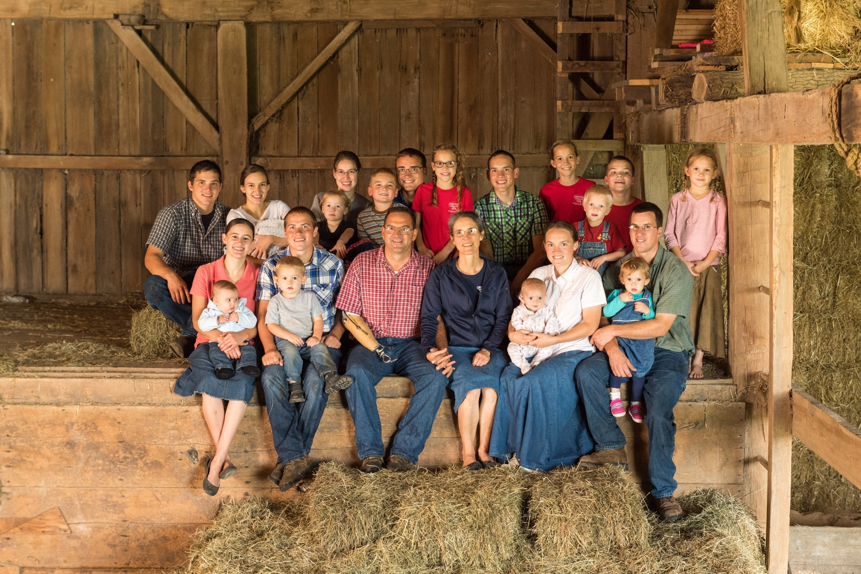 A portrait of a farm family made up of 23 adults, children and infants seated in their barn surrounded by hay bales.