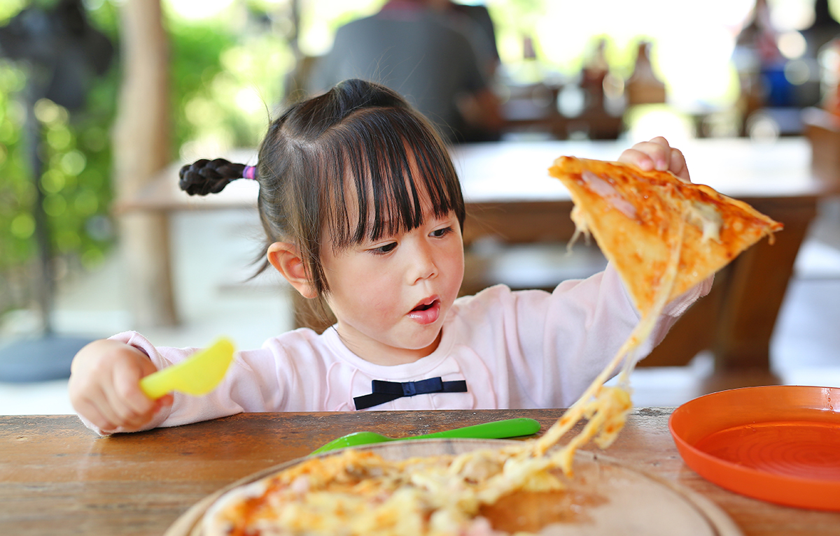 Young Asian girl grabs a piece of cheesy pizza.