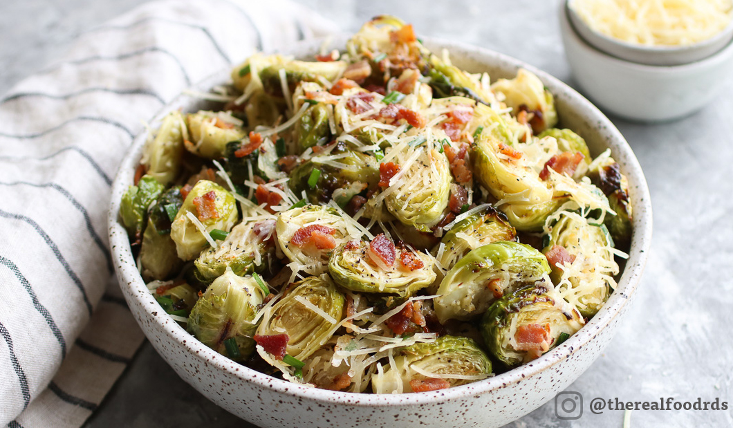 Bowl of roasted Brussels sprouts sprinkled with shredded parmesan and bacon bits.