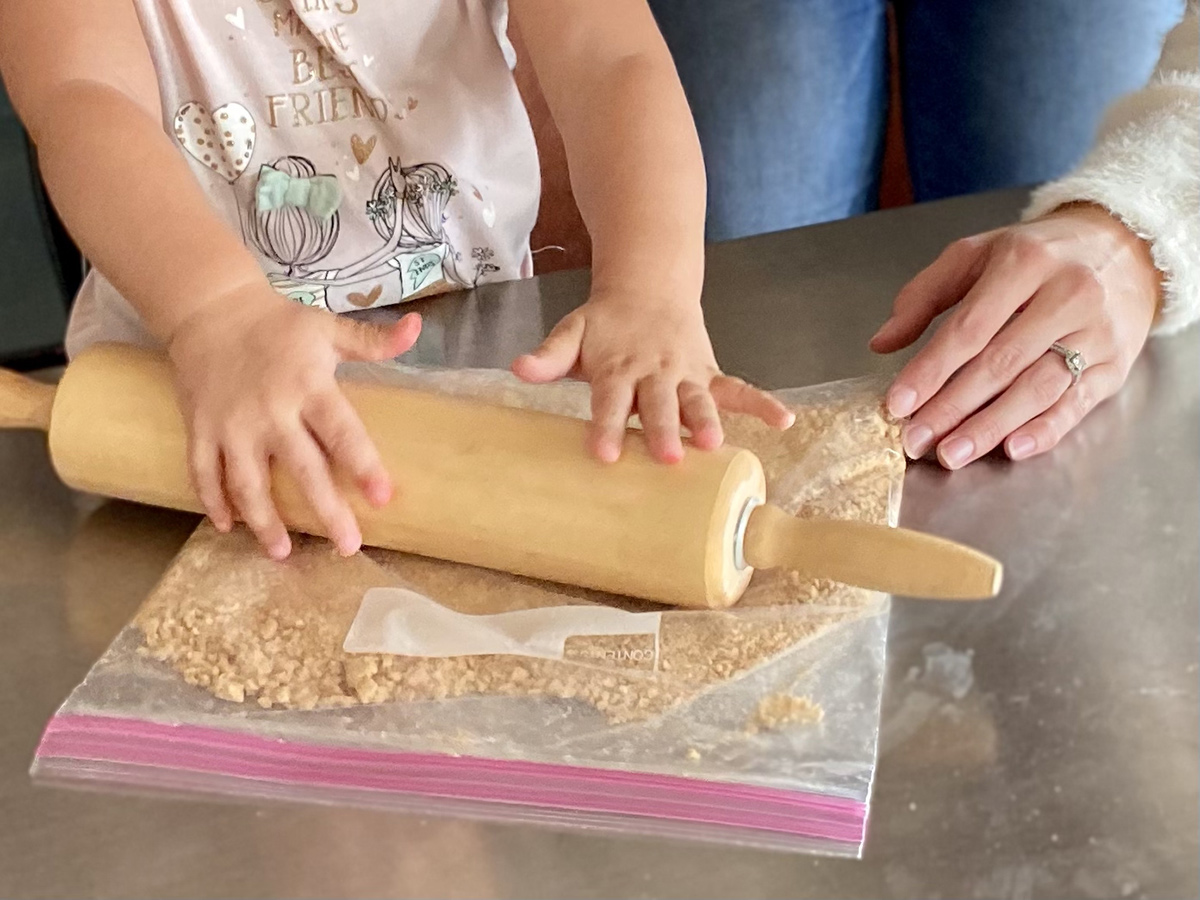 View of a little girl's hands using a rolling pin to smash crackers in a plastic bag.