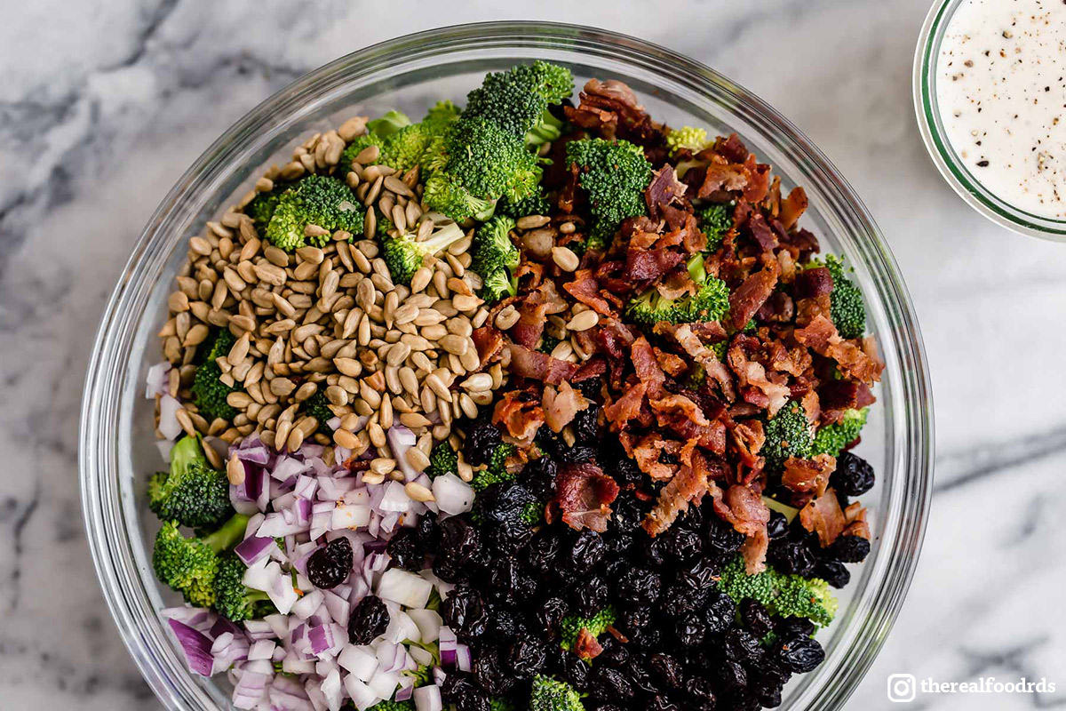 Ingredients for a healthy broccoli salad in a bowl viewed from above on a marble countertop.