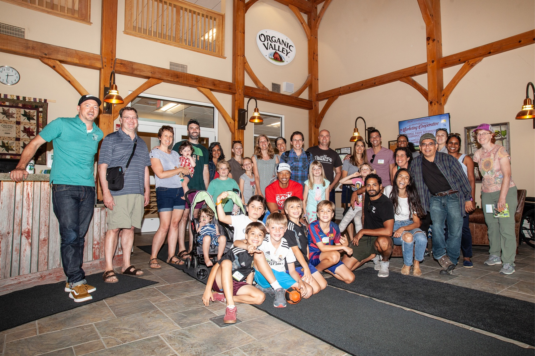 A large group of men, women and children pose in the Organic Valley office building lobby.