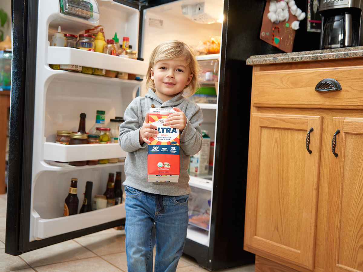 Young boy happily carries a carton of milk in the kitchen.
