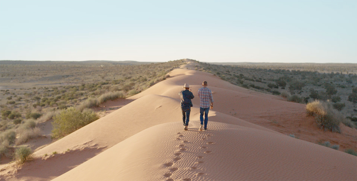 Two men walk along a sand dune rising up from the Australian grasslands.
