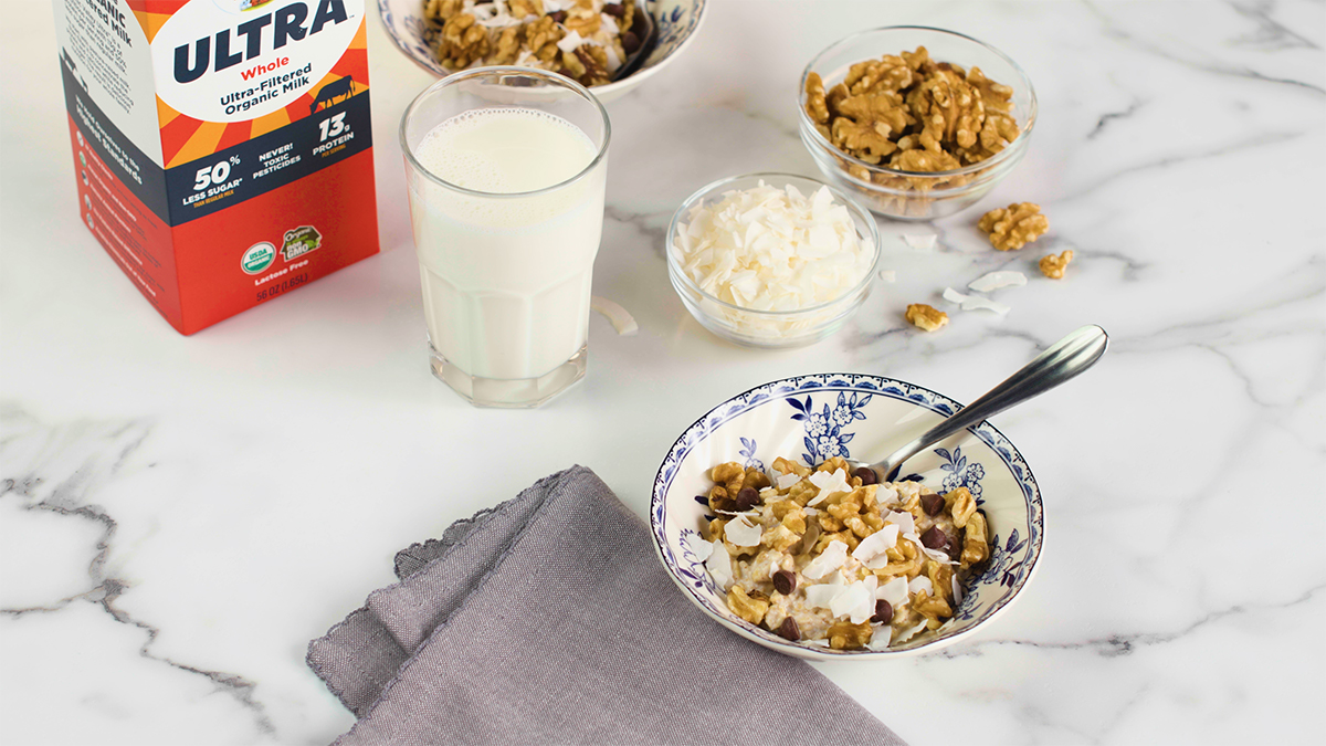 Bowl of oatmeal topped with walnuts, coconut and chocolate chips and Organic Valley Ultra carton sits nearby.
