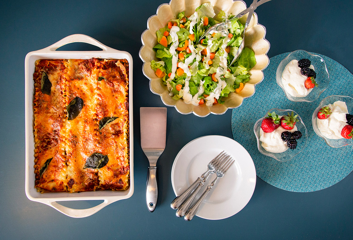A pan of lasagna, salad, and dishes of fruit with whipped cream arranged around plates and forks on a blue table.