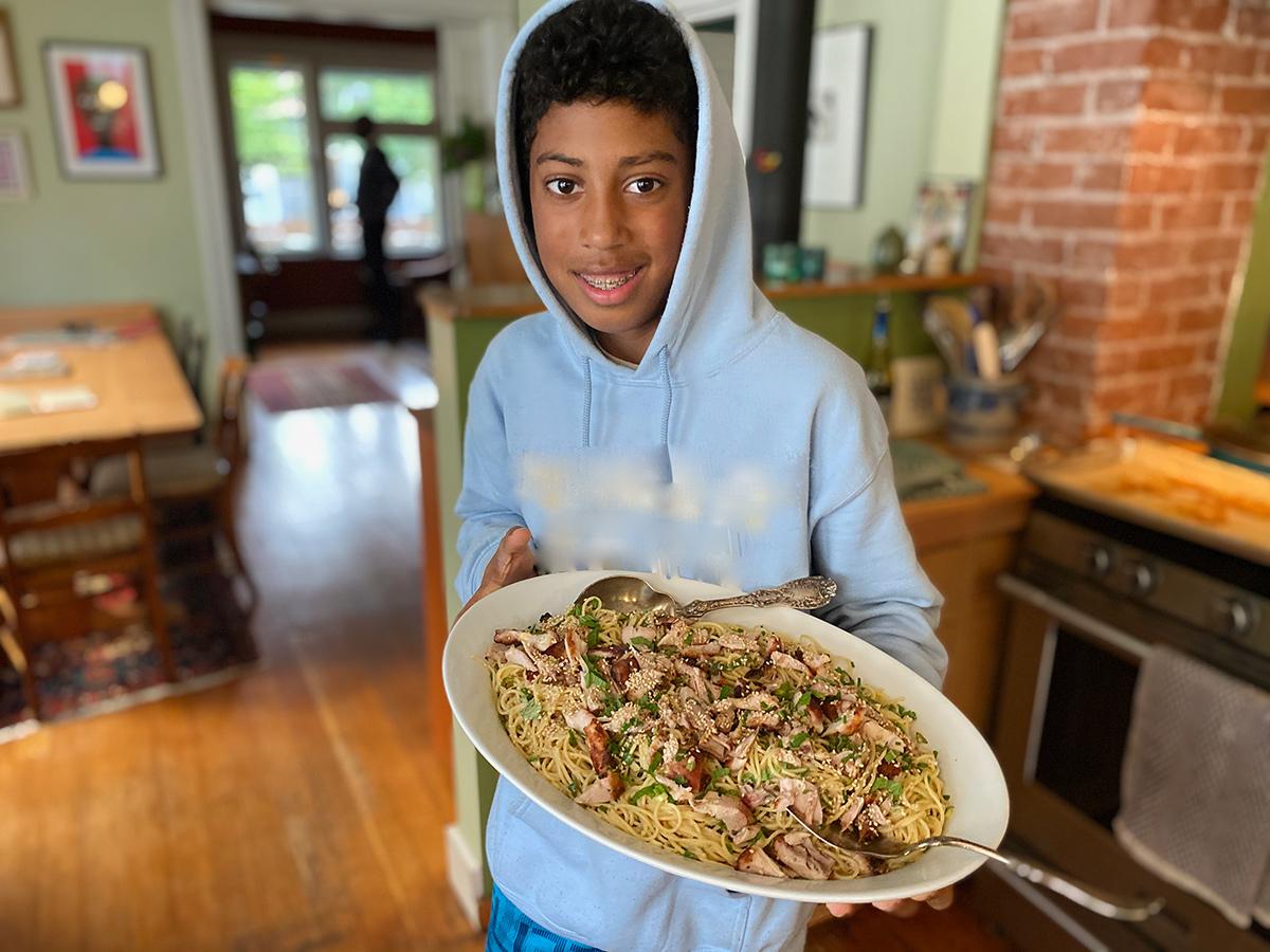 Teenage boy holds up a casserole dish he made.