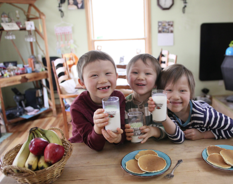 Three young children smile and hold glasses of milk with plates of pancakes in front of them.
