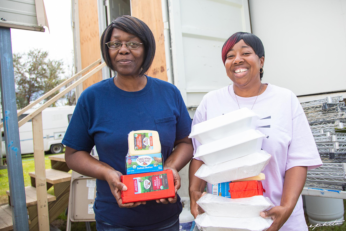 Two women hold packages of Organic Valley cheese and other food.