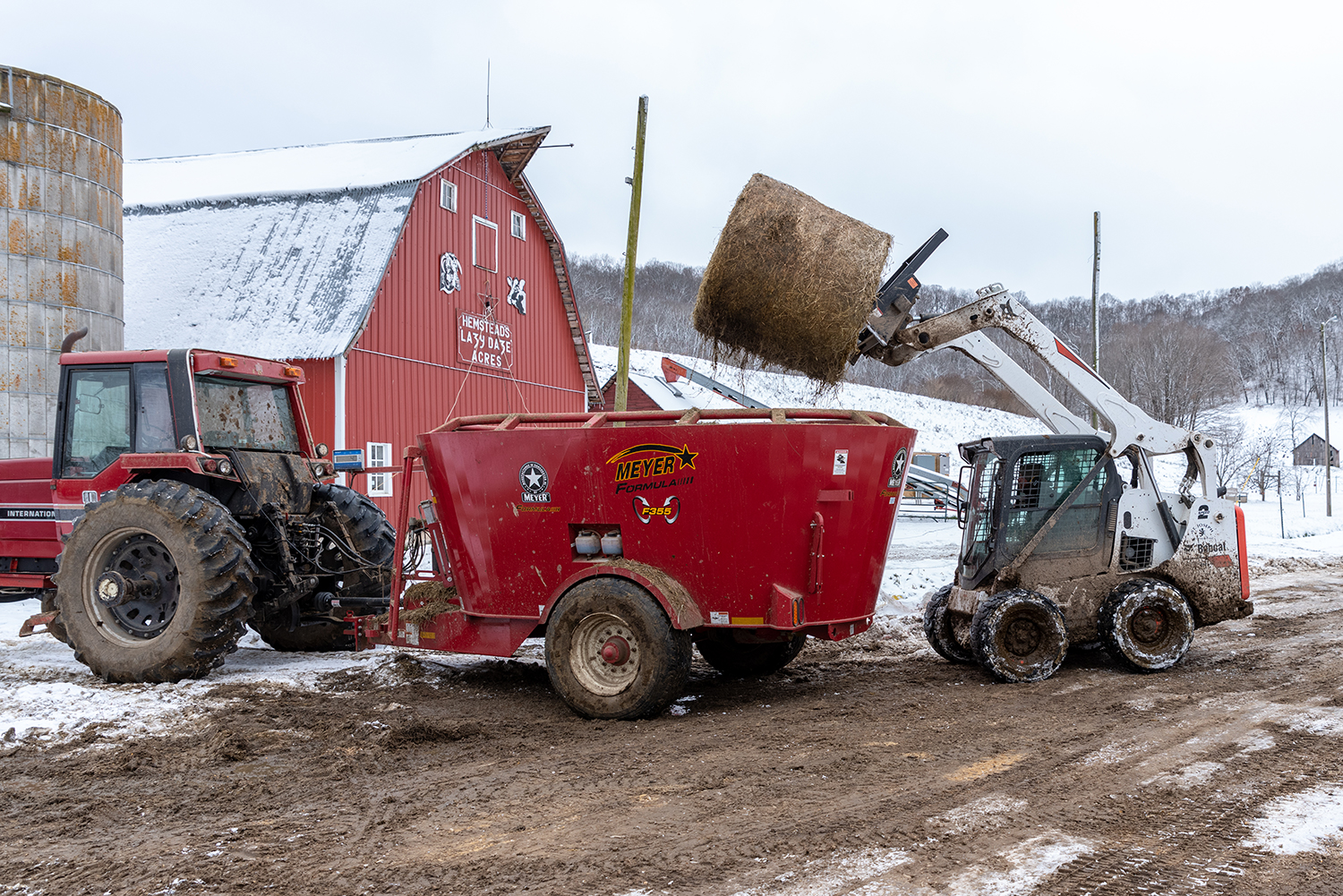 A farmer uses a Bobcat to load a round bale of hay into a trailer pulled by a big tractor.