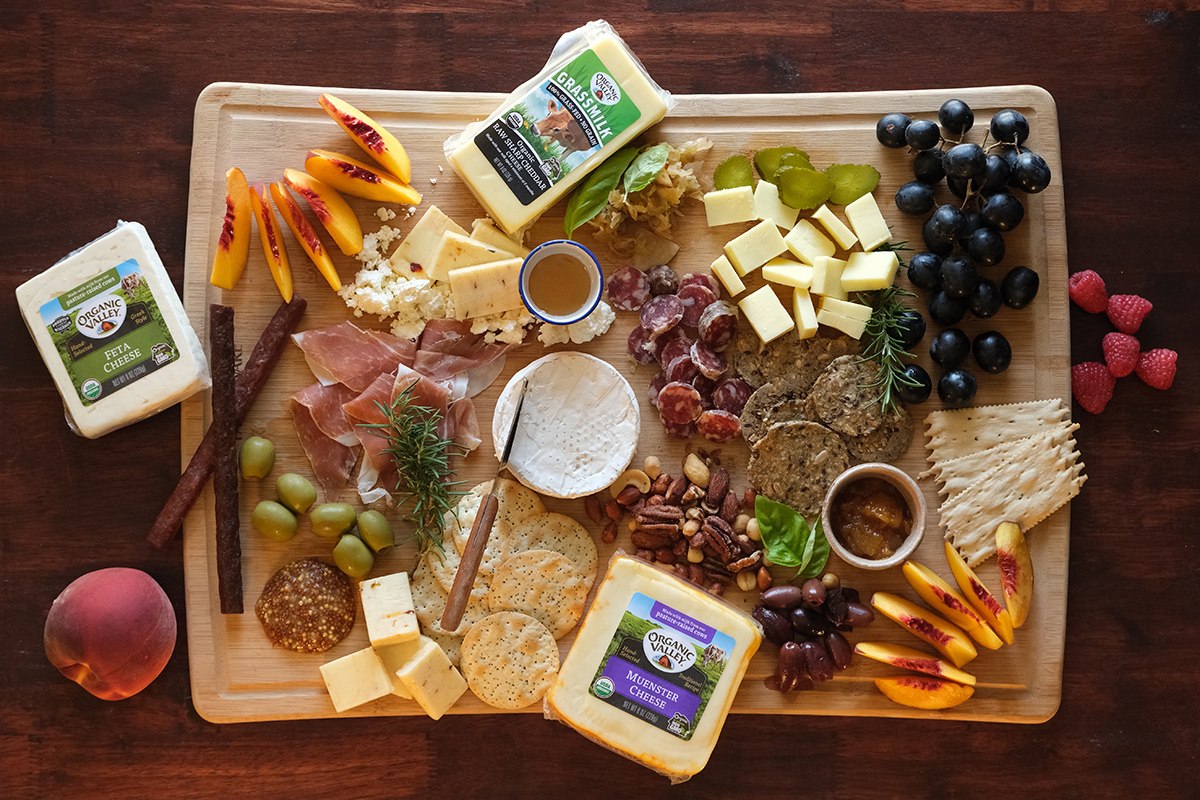 An overhead view of an artful cheese board containing cheese, means, crackers, tips, fruits and nuts.