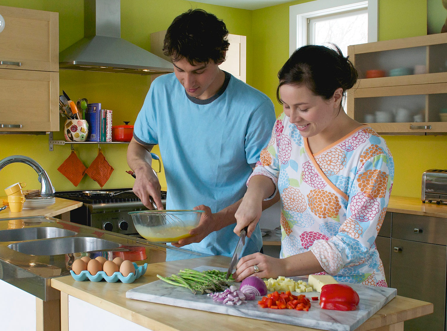 Mom and son make breakfast in the kitchen.