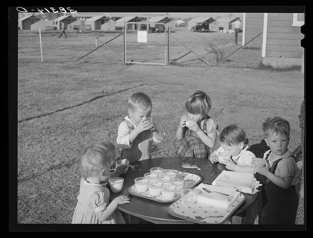 A black and white image of young children drinking milk from a tray on a table outdoors.